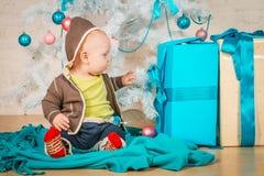 Un bambino con i regali all'albero di Natale Fotografia Stock