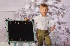 Un bambino con l'albero di Natale e dei regali di Natale fotografie stock