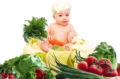 Un bambino con le verdure su un fondo bianco Fotografia Stock