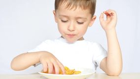 Un bambino con piacere e gioia, mangiando le patatine fritte, sedentesi alla tavola su un fondo bianco, primo piano archivi video