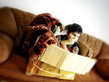 Un bambino creativo su un sofà immagine stock