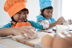 Un bambino di due ragazze imparare cottura e produrre una certa pasta fotografia stock libera da diritti