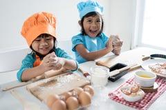 Un bambino di due ragazze imparare cottura e produrre una certa pasta immagini stock