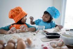 Un bambino di due ragazze imparare cottura e produrre una certa pasta immagini stock libere da diritti