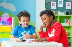 Un bambino di due ragazzi si siede sulla tavola e sul libro di racconto della lettura nel movimento di liberazione prescolare Fotografia Stock Libera da Diritti
