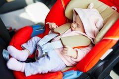Un bambino di mese che dorme nella sede di automobile Fotografie Stock Libere da Diritti