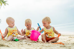 Un bambino di tre bambini che si siede su una spiaggia tropicale in Tailandia e che gioca con i giocattoli della sabbia Le camice Fotografia Stock