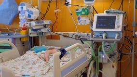 Un bambino dorme in un letto medico in un reparto moderno archivi video