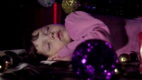 Un bambino dorme sotto l'albero di Natale video d archivio