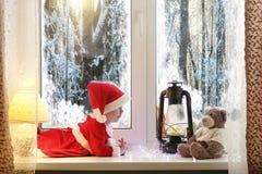 Un bambino durante il nuovo anno guarda fuori la finestra I bambini sono waiti immagini stock