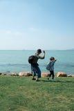 Un bambino e le pietre di lancio del padre fotografie stock libere da diritti
