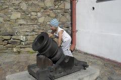Un bambino e un vecchio cannone immagine stock libera da diritti