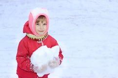 Un bambino esamina la macchina fotografica, neve, in sue mani una palla di neve, contro un fondo di neve bianca Fotografia Stock
