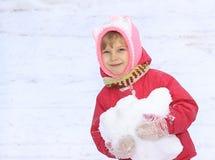 Un bambino esamina la macchina fotografica, neve, in sue mani una palla di neve, contro un fondo di neve bianca Immagine Stock