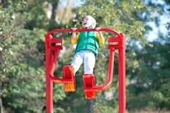 Un bambino fa gli esercizi sui simulatori sulla via Stile di vita attivo fotografia stock