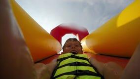 Un bambino fa scorrere giù il waterslide sul suo indietro stock footage