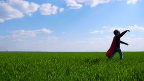 Un bambino felice in un costume del supereroe funziona attraverso un campo verde, tenente la sua mano in avanti stock footage
