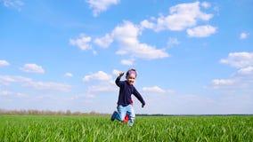 Un bambino felice in un costume del supereroe in un mantello rosso funziona felicemente attraverso un campo verde un giorno soleg stock footage