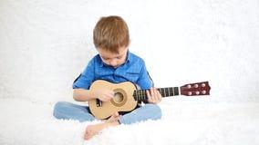 Un bambino felice sta sedendosi su un sofà bianco e sta giocando la chitarra per i bambini archivi video