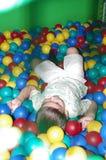 Un bambino felice sta trovandosi sulle palle di plastica immagine stock libera da diritti
