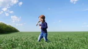Un bambino felice in un vestito pilota del ` s funziona lungo il campo verde, mostrante a rilento le sue mani sul volo dell'aereo stock footage