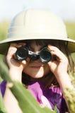 Un bambino in giovane età che osserva tramite il binocolo fotografia stock libera da diritti