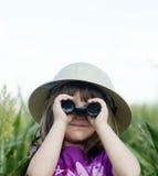 Un bambino in giovane età che osserva tramite il binocolo immagini stock libere da diritti