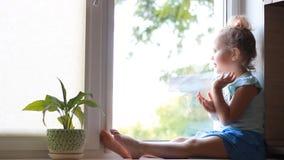 Un bambino guarda fuori la finestra, sorridere, non mostrante gesto Il concetto di aspettativa stock footage