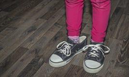 Un bambino indossa le grandi scarpe da tennis nere fotografie stock libere da diritti