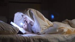 Un bambino legge un libro sotto le coperte con una torcia elettrica alla notte Ragazzo entusiasta stock footage