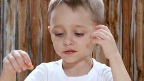 Un bambino mangia le patatine fritte con piacere mentre si siede ad una tavola contro lo sfondo di una parete di legno archivi video