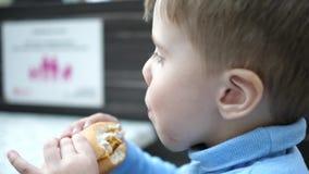 Un bambino mangia un panino con una cotoletta e un formaggio in un fast food video d archivio