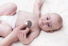 Un bambino molto piccolo, un bambino, si trova indietro all'ambulatorio ed il medico ascolta i polmoni fotografie stock