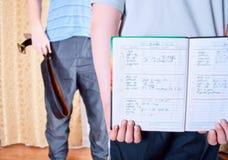 Un bambino nasconde un diario di deuce dal suo padre Fotografia Stock