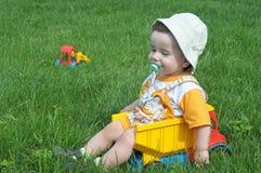 Un bambino nel camion sull'erba Immagini Stock