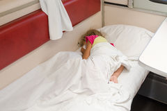 Un bambino nel sonno del treno avvolto in uno strato nel posto più basso nel vagone di seconda classe del compartimento Fotografia Stock