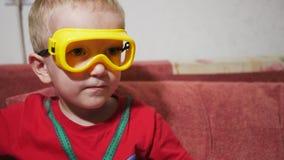 Un bambino in occhiali di protezione si siede sul sofà a casa e guarda la TV Mangi i bastoni ed il sorriso del cereale archivi video