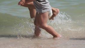 Un bambino in pannolino cammina lungo il litorale in un'acqua, mentre sua madre lo aiuta a muoversi stock footage