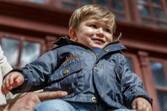 Un bambino piacevole guarda avanti mentre è tenuto da un adulto immagine stock
