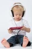 Un bambino piccolo in blue jeans con il gioco delle cuffie Fotografie Stock Libere da Diritti