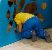 un bambino piccolo oltrepassa, salite, recinta, si trasforma un foro, un taglio, un'apertura in un tessuto blu, nella materia Gio Fotografia Stock