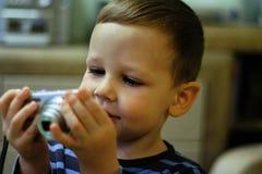 Un bambino piccolo tiene una macchina fotografica nelle suoi mani e sorrisi, sguardi allo schermo immagine stock libera da diritti