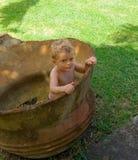 Un bambino piccolo in un vaso antico del ferro fotografie stock
