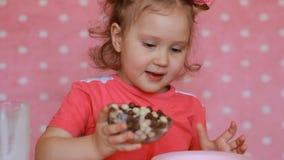 Un bambino prepara la prima colazione per se stesso cereale con yogurt La neonata e mangia l'alimento archivi video