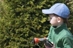 Un bambino, un ragazzo, innaffiante un tubo di gomma in un giardino, una casa di campagna, innaffiante immagine stock