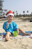Un bambino in Santa Claus copre, Natale su un oceano tropicale è Immagini Stock Libere da Diritti