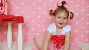 Un bambino in scarpe adulte con i talloni su un fondo rosa Fashionista della ragazza Gambe del bambino in scarpa del ` s della ma stock footage