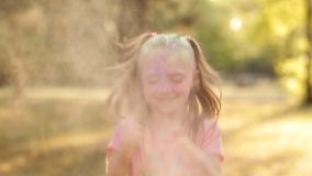Un bambino si diverte il gioco in natura che gioca con le pitture variopinte e la sabbia Agita le sue mani in cui ha colorato la  video d archivio