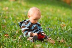 Un bambino si siede nell'erba. Fotografia Stock Libera da Diritti