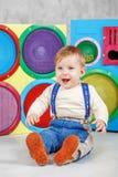 Un bambino si siede sul pavimento e ride Infanzia di concezione, Fotografia Stock Libera da Diritti